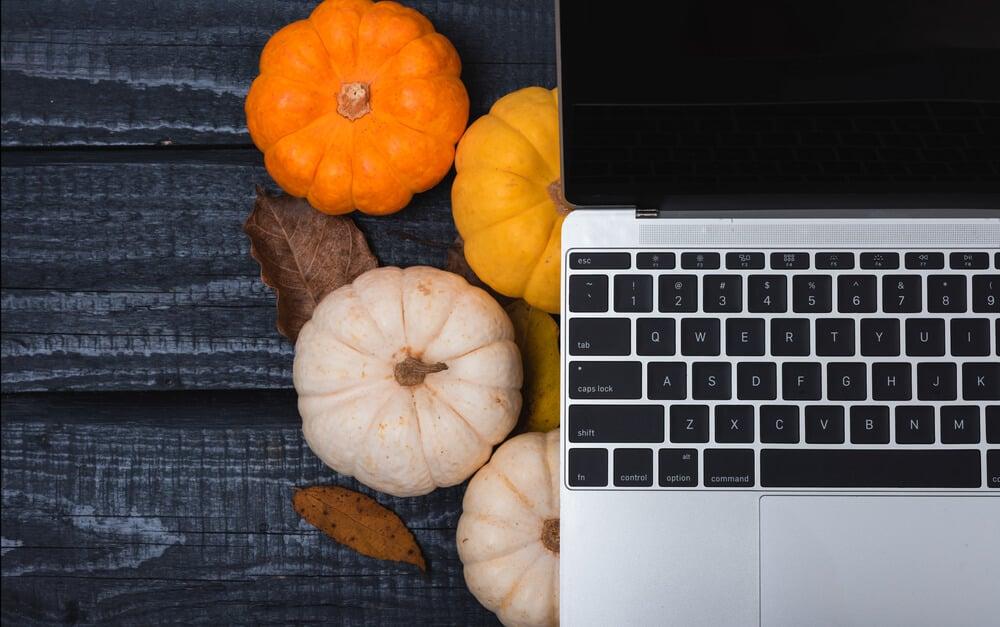 Blogtober! Laptop and pumpkins on blue wooden surface